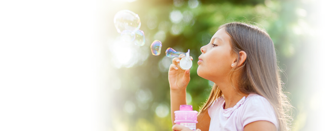 A young girl blowing bubbles.