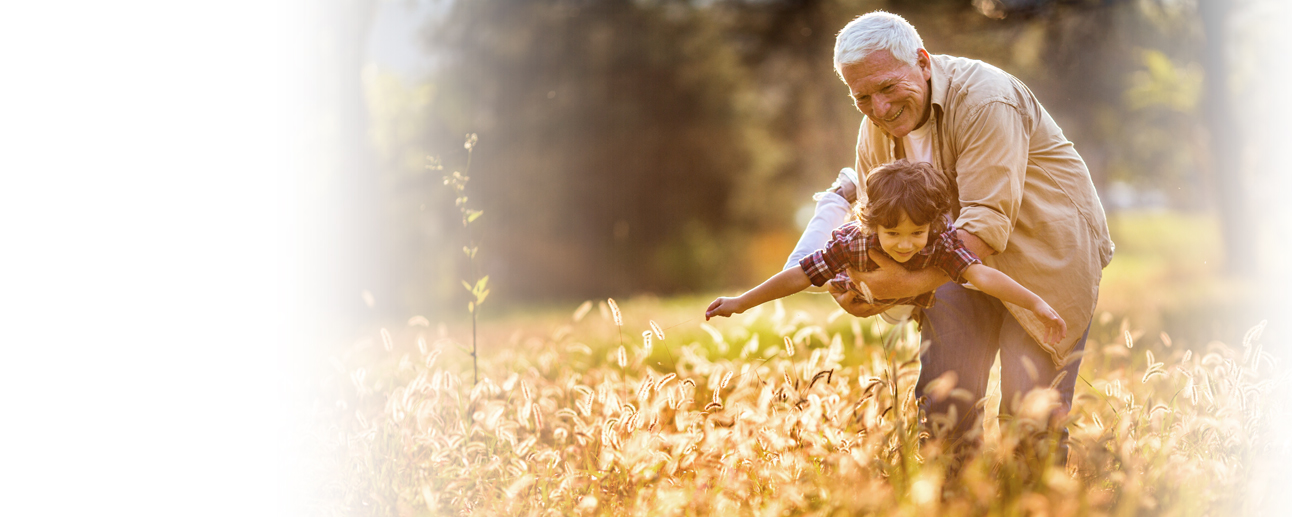 An older man flying a young boy like an airplane through a wheat grass field.