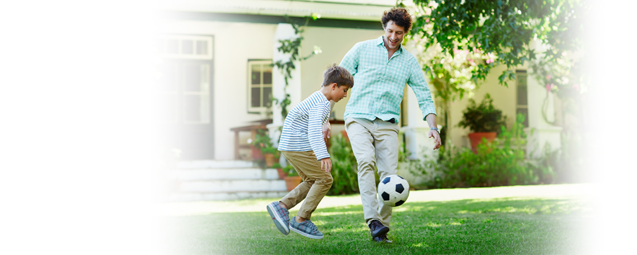 A man and young boy playing soccer outside.